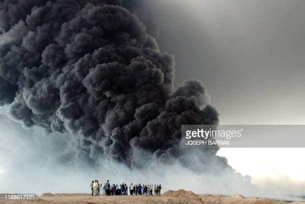 Iraqis watch the fire that broke out on Iraq's oil export pipeline from the southern city of Basra, 500 kilometres from Baghdad, to the Faw peninsula...