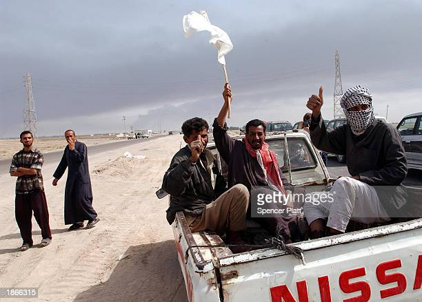 Iraqis wave a white flag on a road where there have been reports of isolated Iraqi military units March 23 2003 south of the Iraqi city of Basra Both...