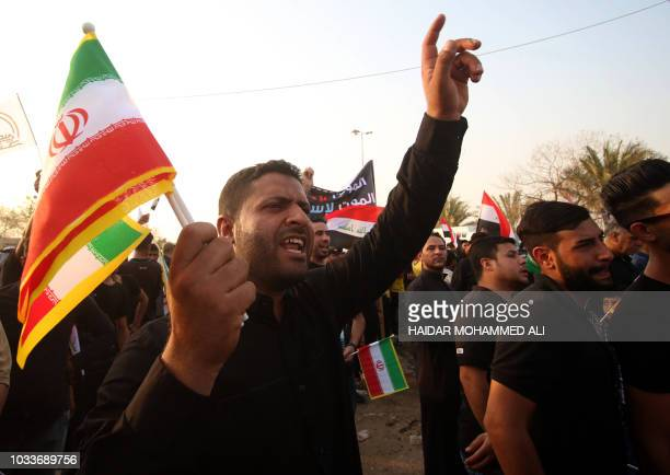 Iraqis wave national and Iranian flags during a protest on September 15 against the torching of the Iranian Consulate and the Hashed alShaabi party...