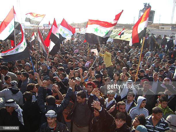 Iraqis wave their national flag during a sitin by citizens clergy tribal leaders and MPs in the northern city of Samarra in Salaheddin province close...