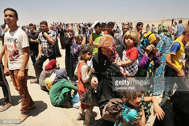 Iraqis who have fled recent fighting in the cities of Mosul and Tal Afar try to enter a temporary displacement camp but are blocked by Kurdish...