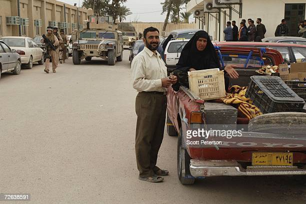 Iraqis with a patient lying in the back of a truck gesture as US Marines of the 4th Civil Affairs Group visit the Fallujah General Hospital on...