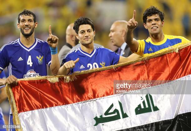 Iraq's Air Force Club players Suad Natiq Naji Mohammed Hasan and Fahad Talib Raheem hold their national flag as they celebrate after beating India's...