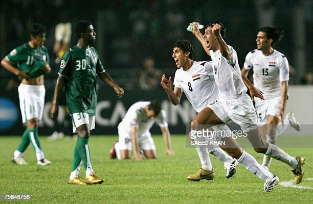 Iraq's captain Younis Mohmoud and teammates run past dejected Saudi Arabia's players as they celebrate their victory at the end of the final match of...