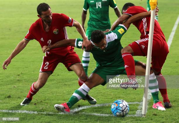 Iraq's defender Ali Adnan controls the ball as he is marked by Jordan's defenders Feras Shelbaieh and Yasser AlRawashdeh during their international...