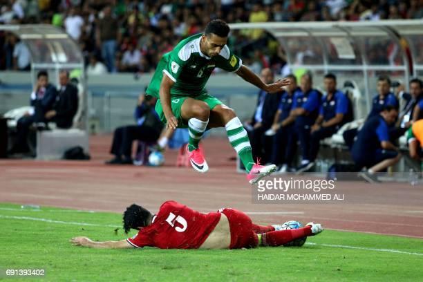 Iraq's defender Ali Adnan jumps over a tackle by Jordan's defender Ibrahim AlZawahreh during their international friendly football match between Iraq...