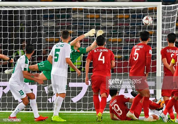 Iraq's defender Ali Adnan kicks a free kick and scores a goal as Vietnam's goalkeeper Van Lam Dang dives during the 2019 AFC Asian Cup group D...