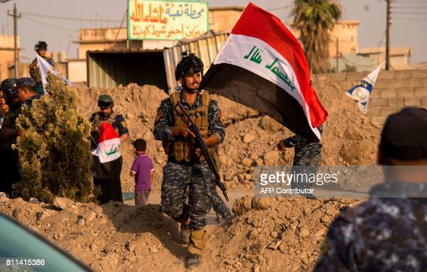 Iraq's federal police members wave Iraq's national flag as they celebrate in the Old City of Mosul on July 9 2017 after the government's announcement...