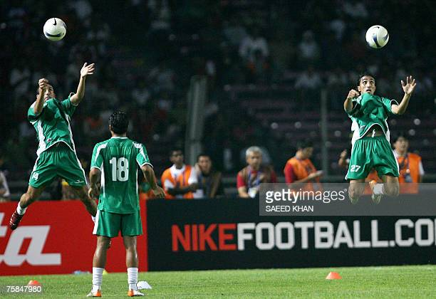 Iraq's Haidar Abdul Amer and Emad Mohamed leap in the air to head balls as they warm up before the start of the final match of the Asian Football Cup...