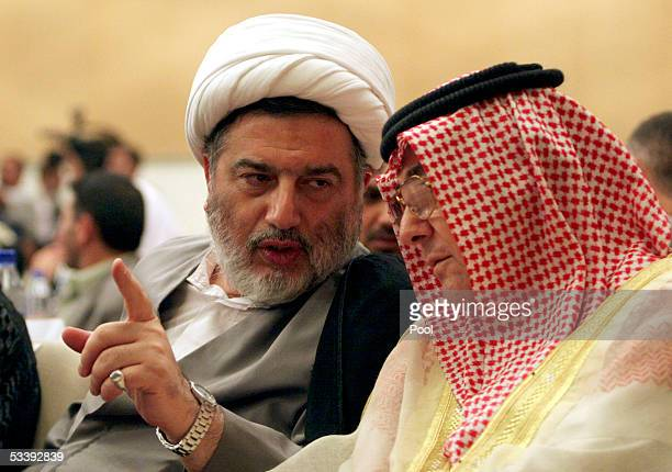 Iraq's leader of the constitution draft committee Humam Hamoudi speaks with Shiite United Iraqi Allies' political leader Sami alMajoun during a...