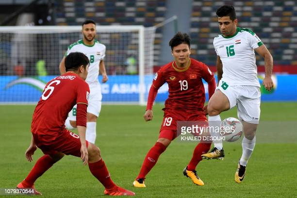 Iraq's midfielder Hussein Ali fights for the ball with Vietnam's midfielder Quang Hai Nguyen and Vietnam's midfielder Xuan Truong Luong during the...