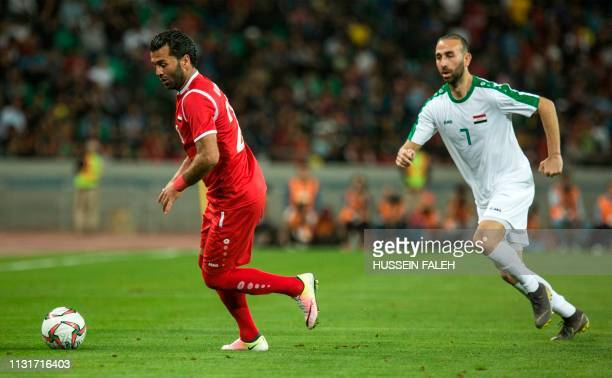 Iraq's midfielder Justin Meram fights for the ball against Syria's forward Mohamed Al Wakid during the international friendly football match between...