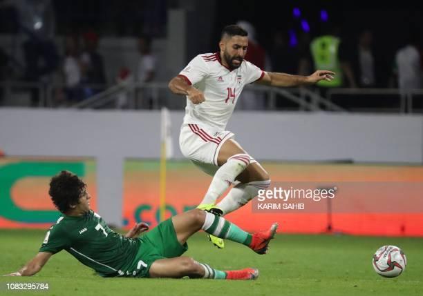 Iraq's midfielder Safaa Hadi AlFuraiji attempts to tackle Iran's midfielder Saman Ghoddos during the 2019 AFC Asian Cup group D football match...