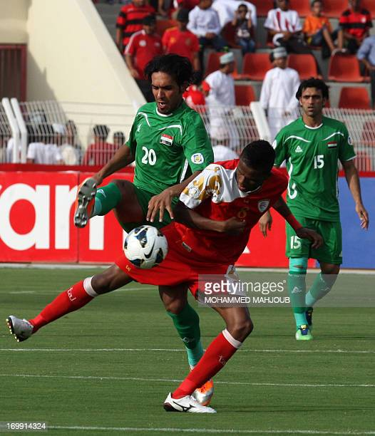 Iraq's Muthana Khalid is challenged by Oman's Eid alFarsi during their group B Asian zone qualifying football match for the 2014 World Cup in Muscat...