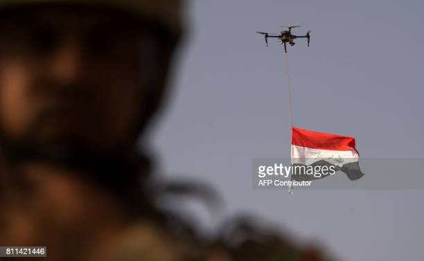 TOPSHOT Iraq's national flag is suspended to a drone of Iraq's federal police as forces celebrate in the Old City of Mosul on July 9 2017 after the...