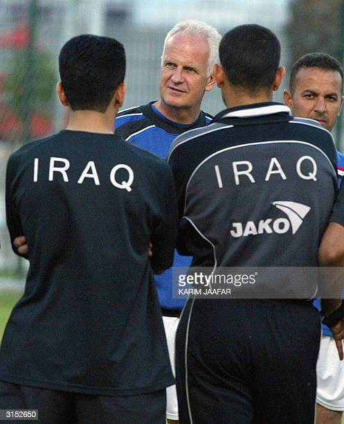 Iraq's national soccer team coach Bernd Stang of Germany instructs 29 March 2004 his players at alIttihad stadium in Doha during a training session...