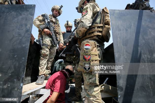 TOPSHOT Iraqs rapid response forces detain a man as they storm a house in the Tarmiyah district north of Baghdad searching for wanted Islamic State...