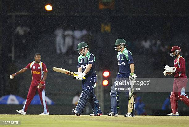 Ireland batsman Paul Stirling and Ed Joyce leave the ground as rain stops the game during the ICC T20 World Cup cricket match between West Indies and...