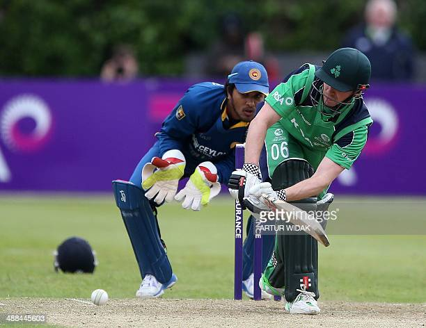 Ireland captain William Porterfield plays a shot as Sri Lanka's Lahiru Thirimanne looks on from behind the stumps during a One Day International...