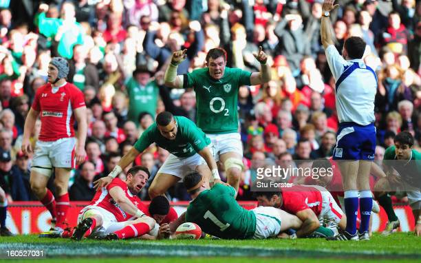 Ireland celebrate their second try scored by Cian Healy as the Wales players Alex Cuthbert and Mike Phillips look on dejectedly during the RBS Six...