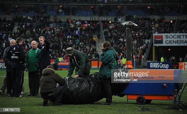 Ireland Coach Declan Kidney talks to the officials as groundsmen use a heater to warm area's of the pitch during the RBS 6 Nations match between...