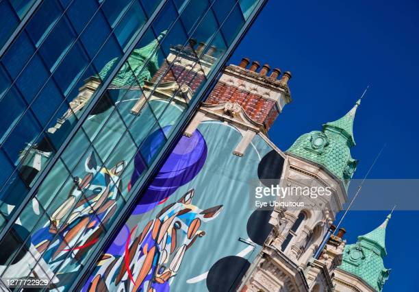 Ireland, County Antrim, Belfast, Towers of the National Bar and Restaurant reflected in a modern glass building.