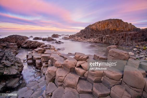 Ireland. County Antrim. Giants Causeway. Dramatic colourful cloud pattern over the rocks at sunrise.