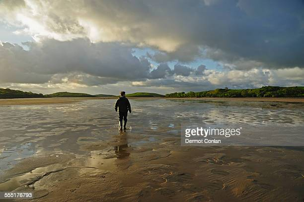Ireland, County Mayo, Clew Bay, Rear view of man standing water in rubber boots, clouds in sky