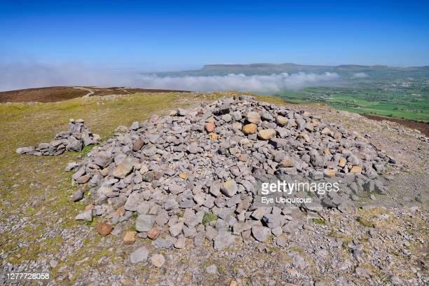 Ireland, County Sligo, Ben Bulben mountain seen from the summit of Maeve's Cairn on Knocknarea mountain with sea fog rolling in.