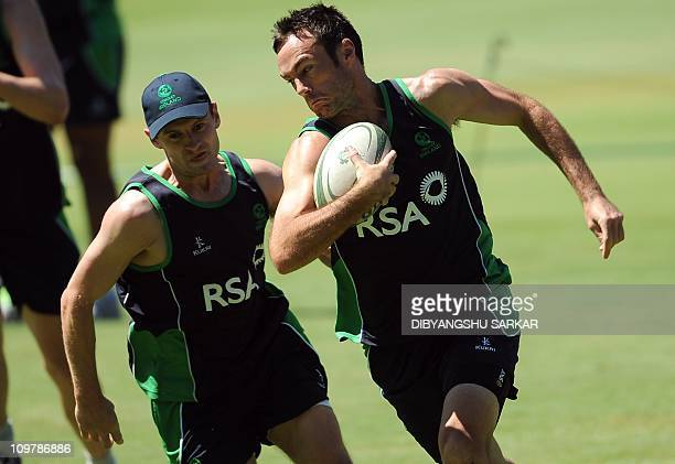 Ireland cricketer Nigel Jones and captain William Porterfield play a game of rugby during a training session at the M Chinnaswamy Stadium in...