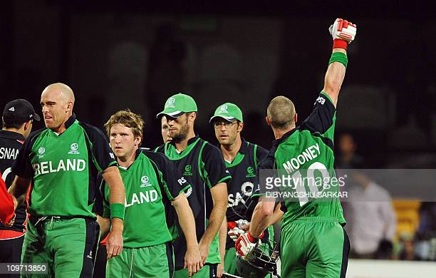 Ireland cricketer Trent Johnston with teammates shakes hand with England cricketers as they celebrate Ireland's win during the ICC Cricket World Cup...