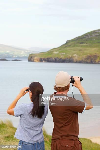 Ireland, Donegal, Ballymastocker Bay couple using binoculars
