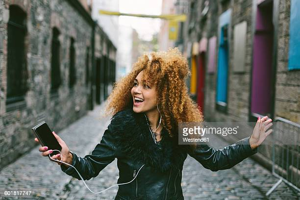 Ireland, Dublin, happy woman with afro hearing music with smartphone and earphones