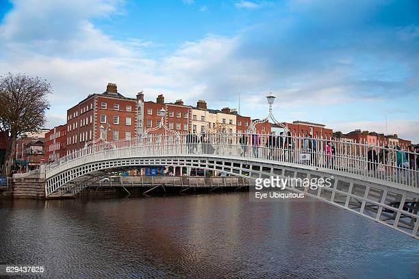 Ireland Dublin People crossing the Ha'penny Bridge across River Liffey viewed from the Temple Bar side
