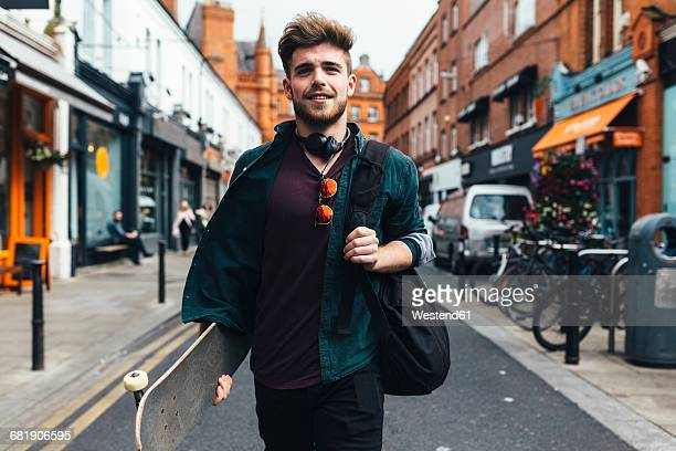 Ireland, Dublin, portrait of young man with skateboard walking on the street