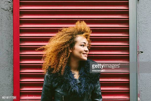 ireland, dublin, smiling woman with afro in front of red roller shutter - hair colour stock pictures, royalty-free photos & images