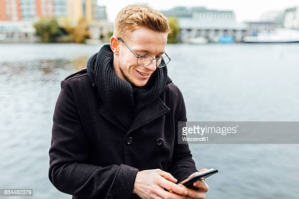 Ireland, Dublin, smiling young man looking at his smartphone in front of the water