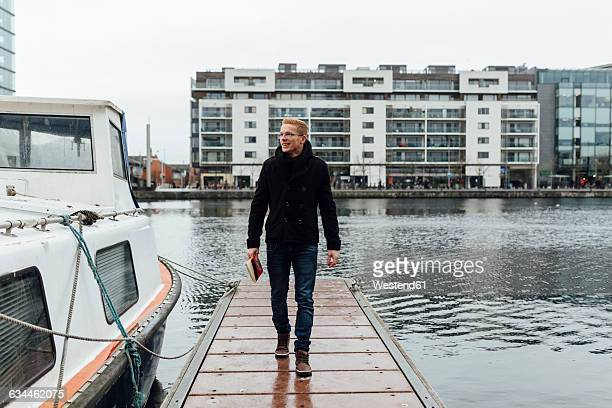 Ireland, Dublin, smiling young man with a book walking on a jetty in winter