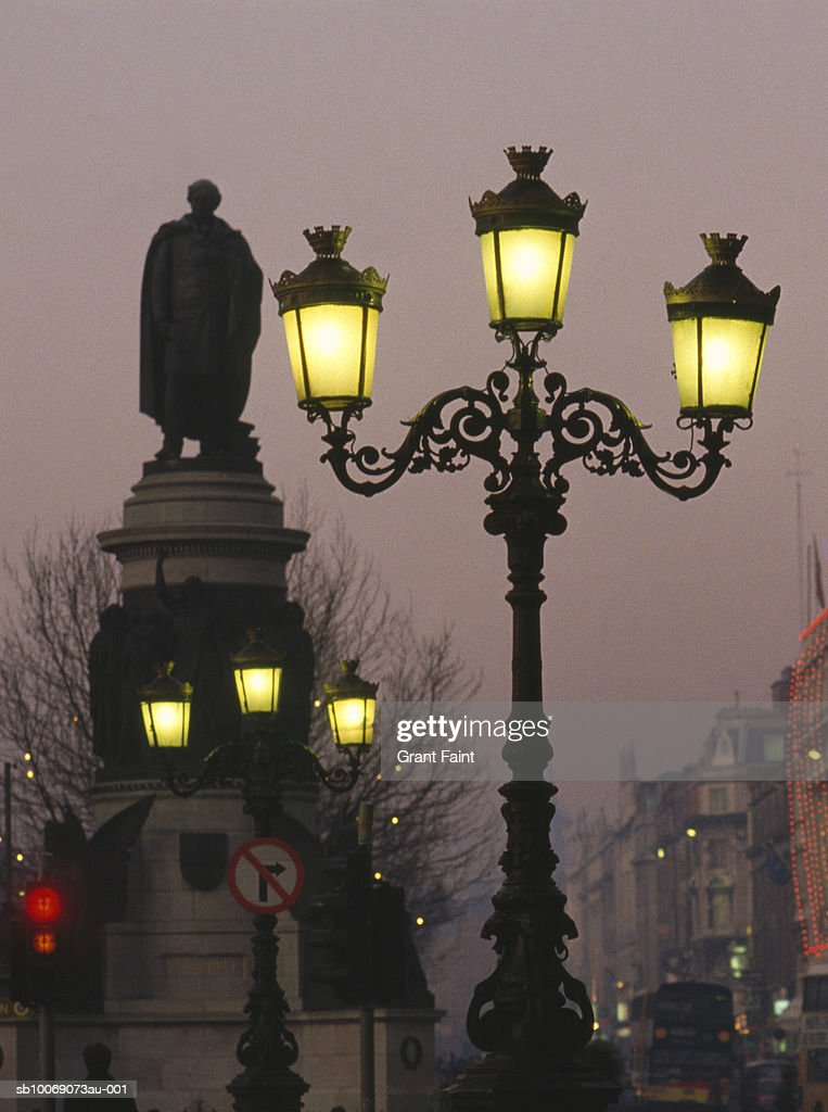 Ireland, Dublin, street lamps in front of statue at dusk : Stockfoto