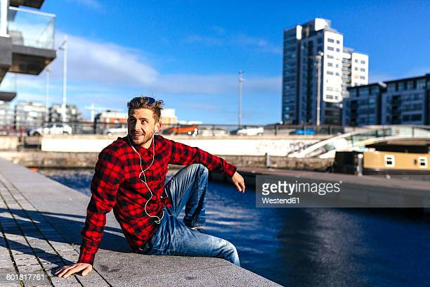 Ireland, Dublin, young man at city dock listening to music