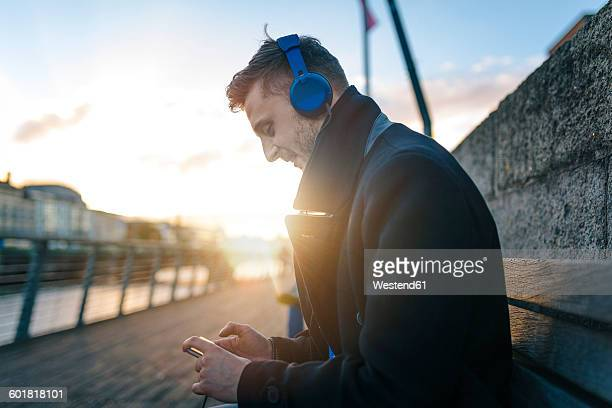 Ireland, Dublin, young man sitting on a bench at backlight hearing music with headphones