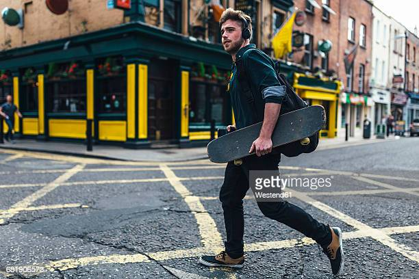 Ireland, Dublin, young man with headphones and skateboard crossing the street