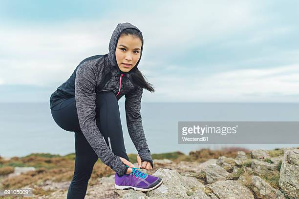 Ireland, Howth, woman lacing her shoes at cliff coast