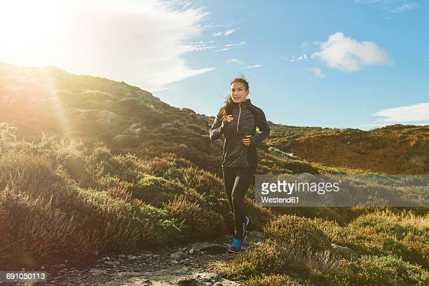 ireland, howth, woman running on coastal path - joggeuse photos et images de collection