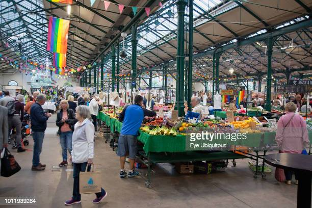 Ireland North Belfast St George's Market interior Fruit and veg stalls with rainbow flags above