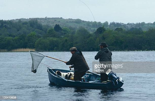 Ireland Paul and Ciaran Cullen and dog Barney netting a nice trout on Lough Arrow