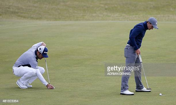 Ireland's amateur golfer Paul Dunne and South Africa's Louis Oosthuizen putt on the 12th green during his third round 66, on day four of the 2015...
