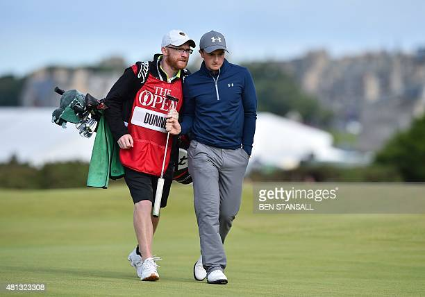 Ireland's amateur golfer Paul Dunne talks to his caddie Alan Murray as they walk up the 16th fairway during his third round 66, on day four of the...