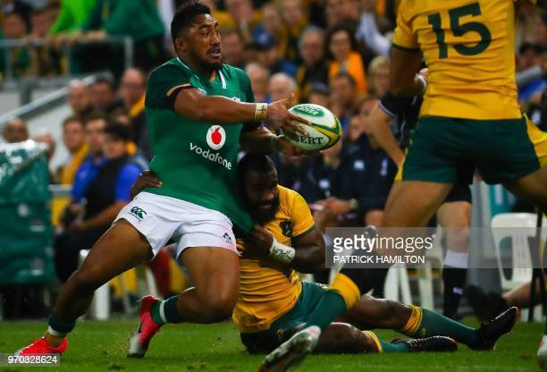 Ireland's Bundee Aki is tackled by Australia's Marika Koroibete during the first rugby Test between Australia and Ireland at Suncorp Stadium in...
