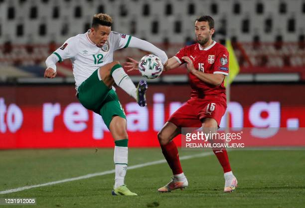 Ireland's Callum Robinson fights for the ball with Milan Gajic of Serbia during the FIFA World Cup Qatar 2022 qualification football match between...